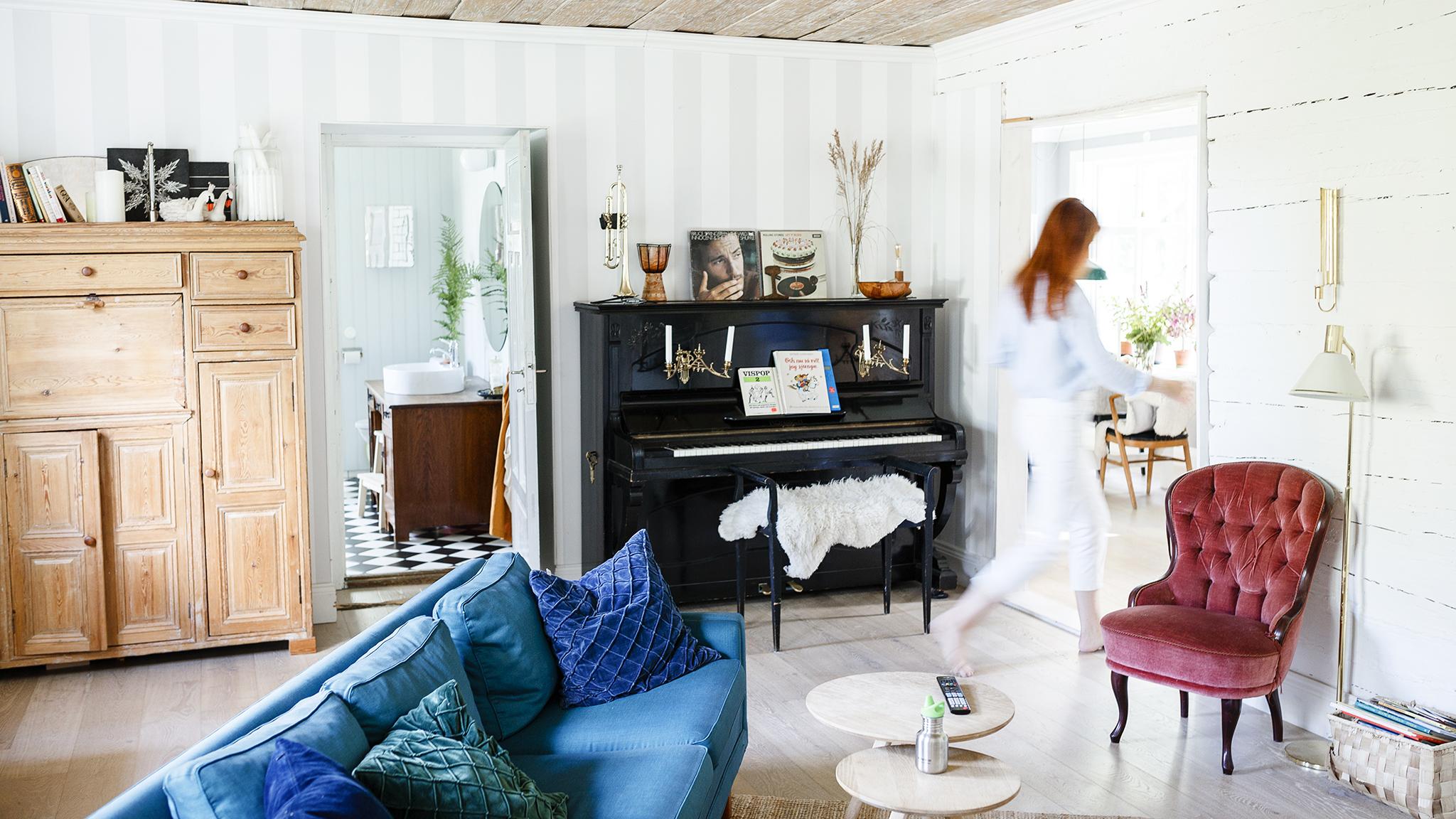 vardsgsrum med blå soffa, svart piano och en rosa emma-fåtölj.