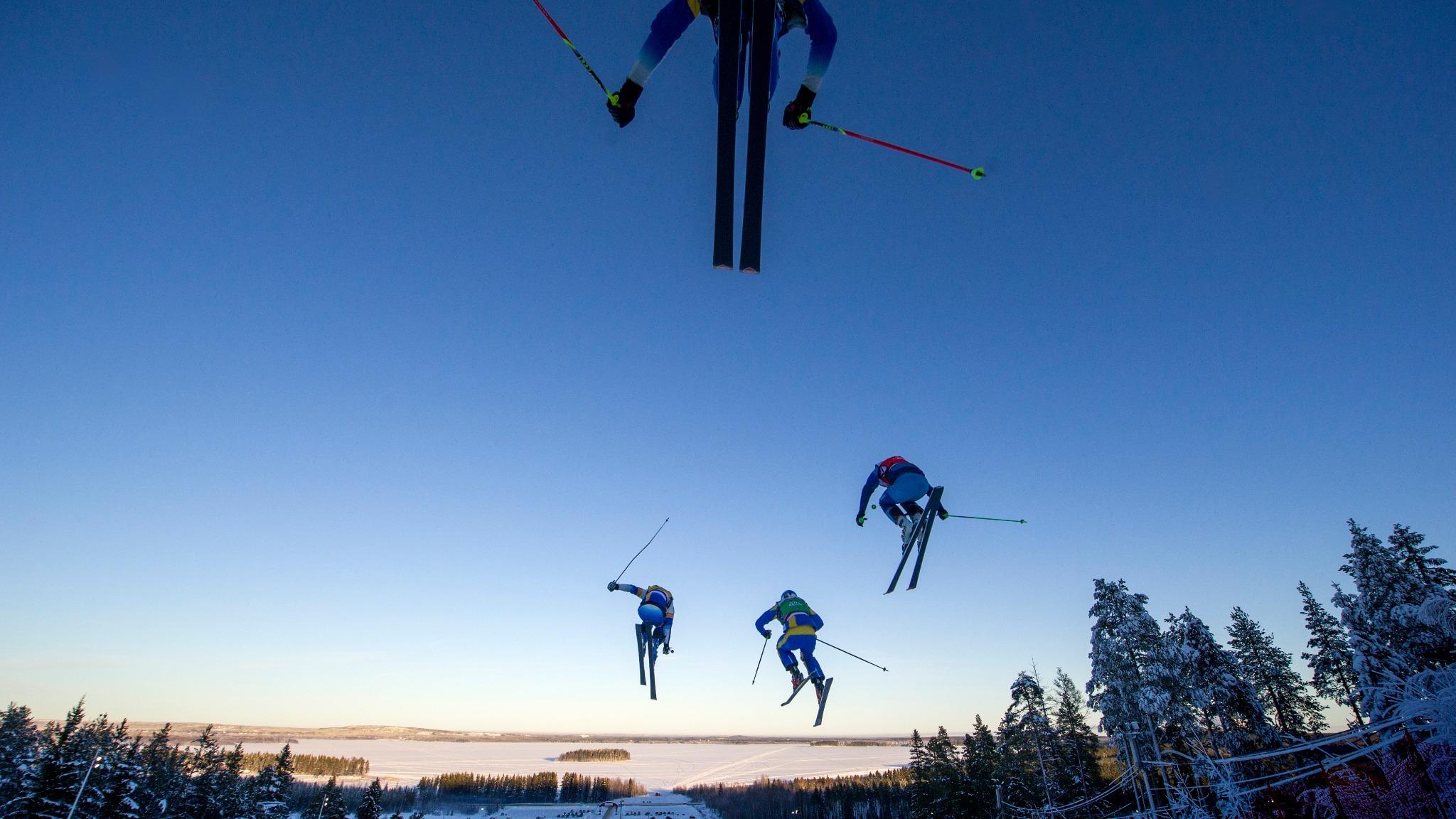 Fyra skidåkare flyger genom luften.