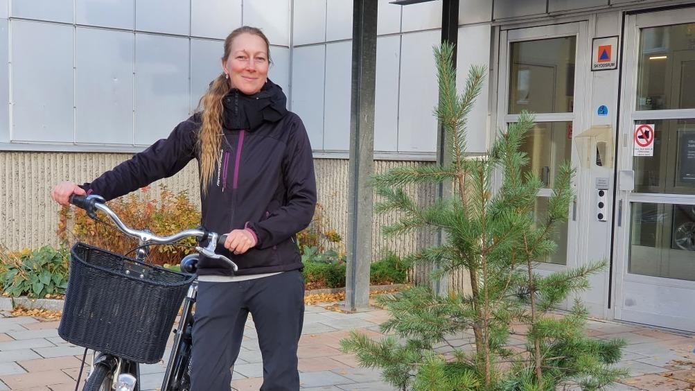 Står en kvinna med cykel