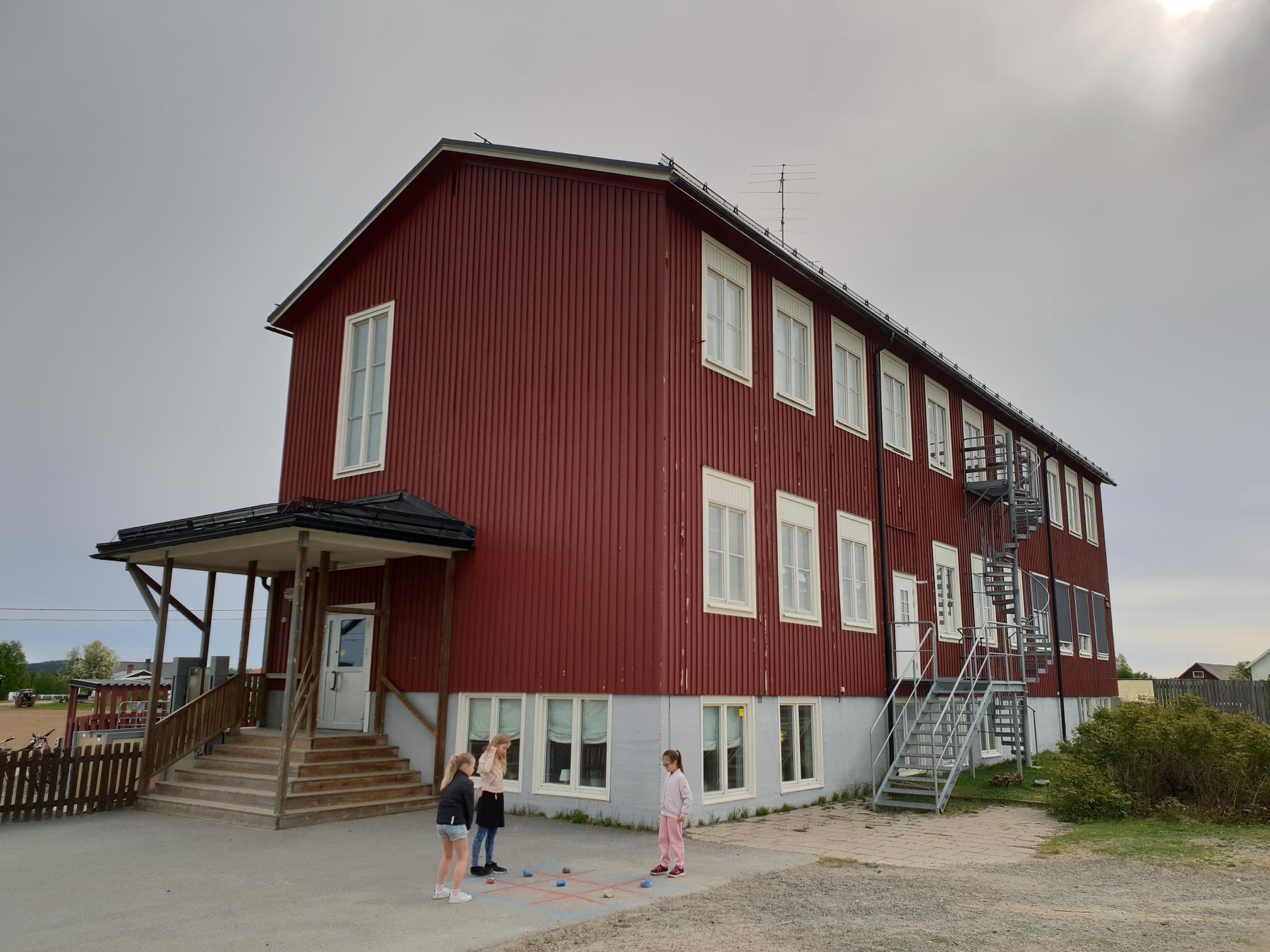 Röd skolbyggnad med tre barn framför.