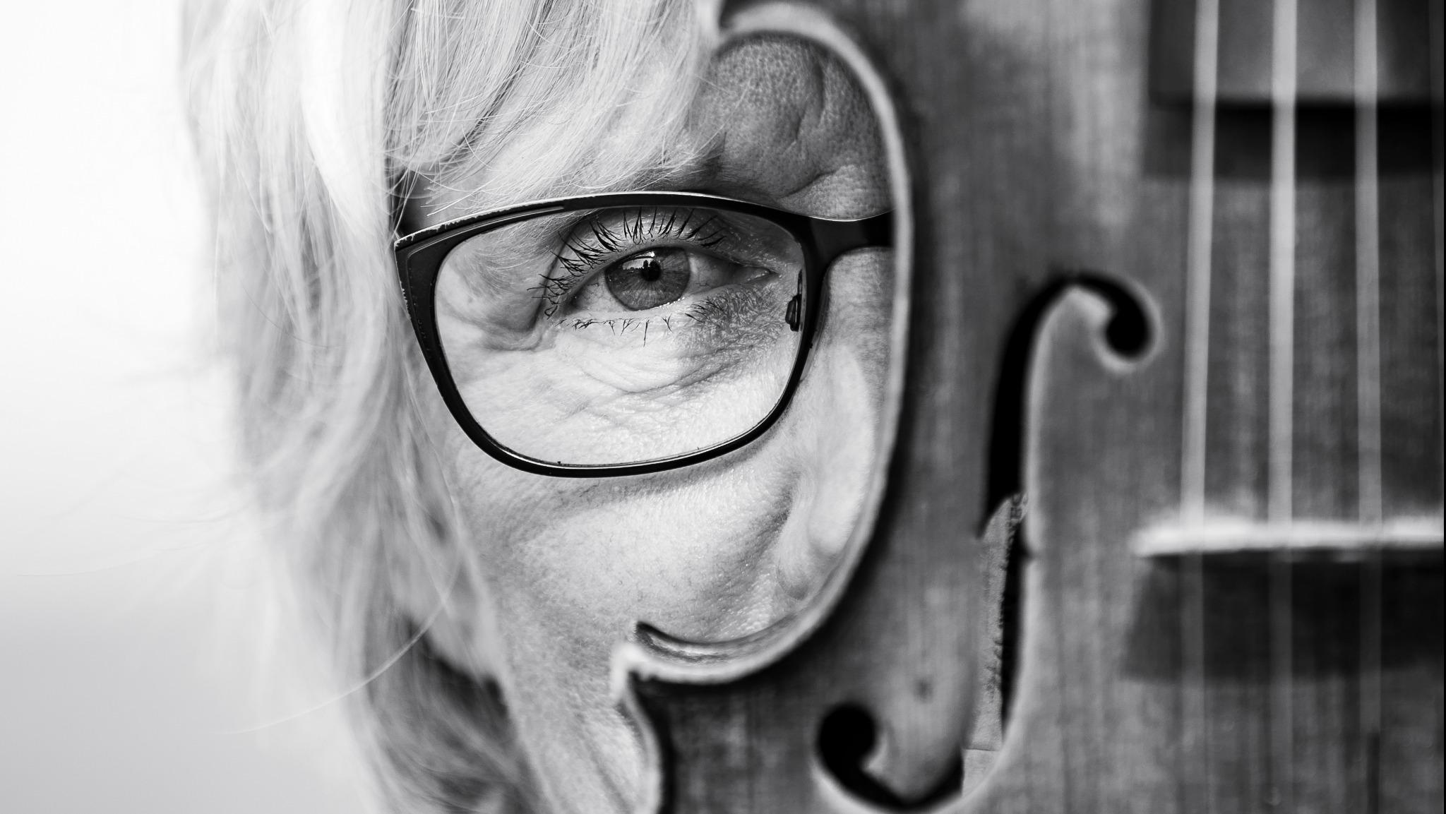 Svartvit närbild på ett delvis dolt ansikte bakom en fiol.