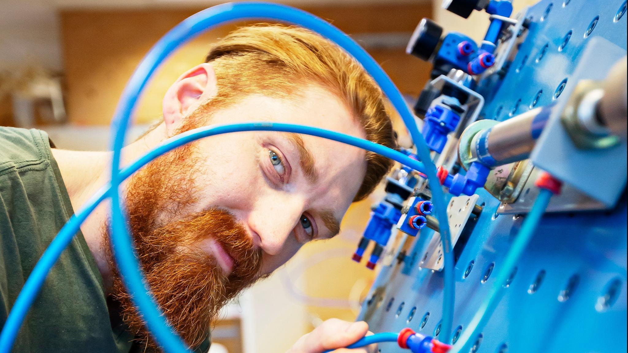 En person som håller på att utbilda sig till elektriker står vid en blå el tavla.