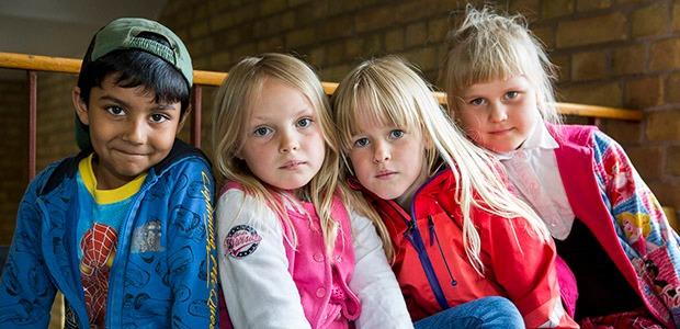 Fyra barn i färgglada kläder tittar in i kameran.