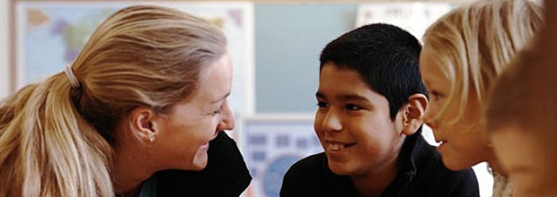 Blond kvinna pratar med pojke i ett klassrum. En ung flicka tittar på.