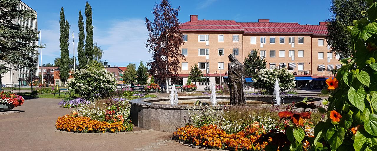Bodens blommande stadspark i solsken med fontänen i förgrunden