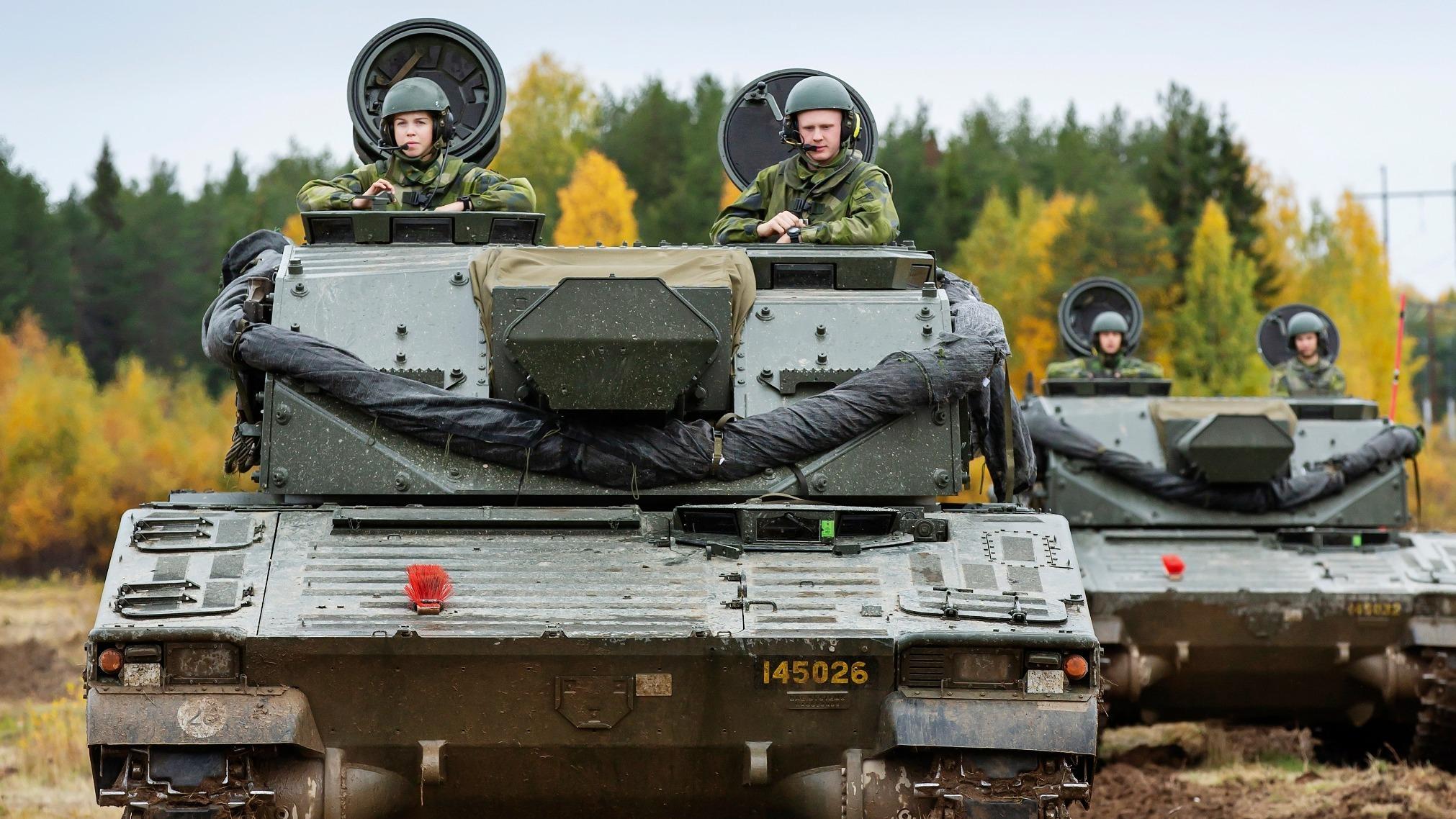 två granatkastarpansarbandvagnar i terrängen