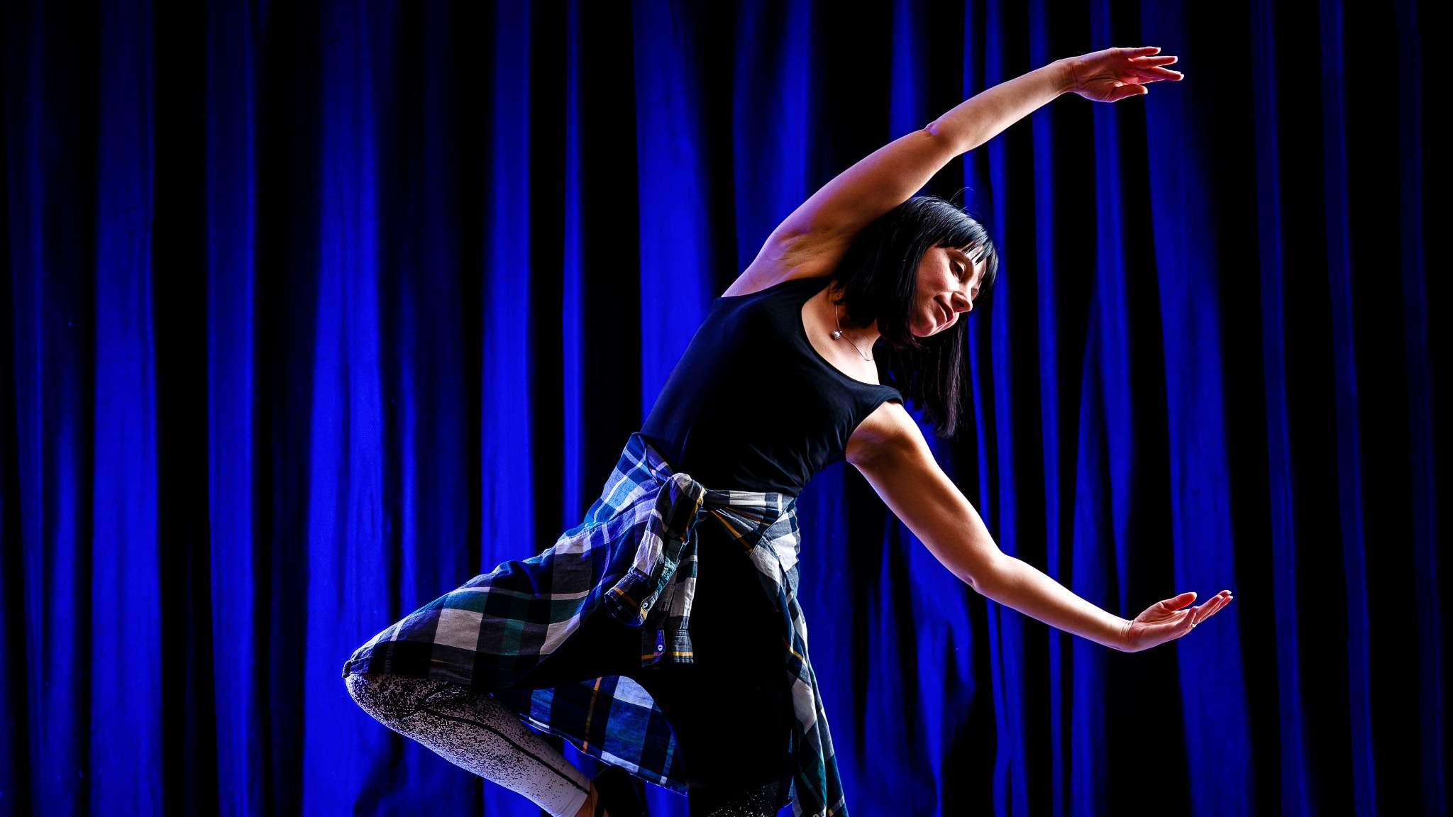mörkhårig kvinna i danspose mot blå bakgrund