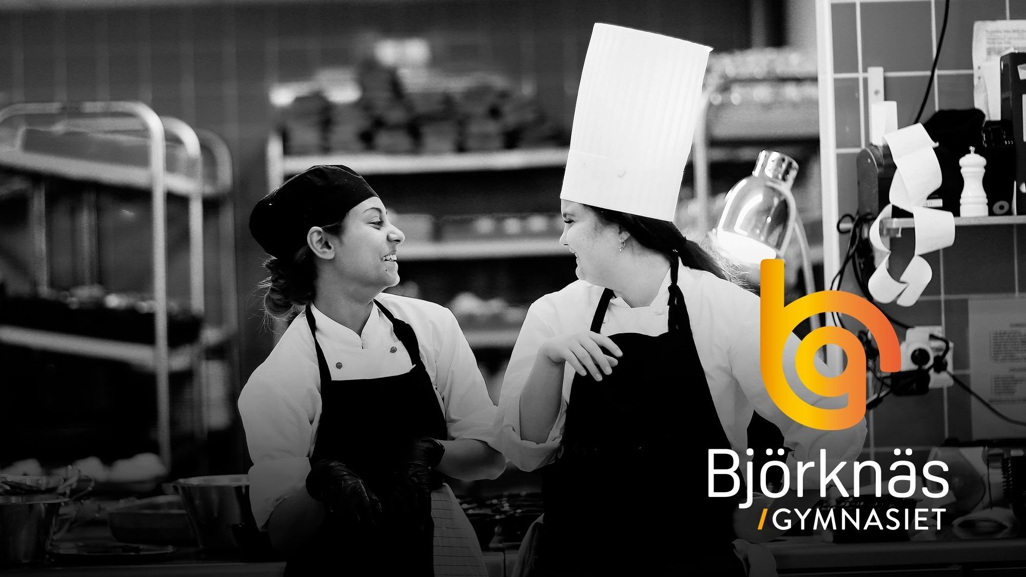 Två tjejer som går restaurang och livsprogrammet som står och skrattar i kockkläder i köket.