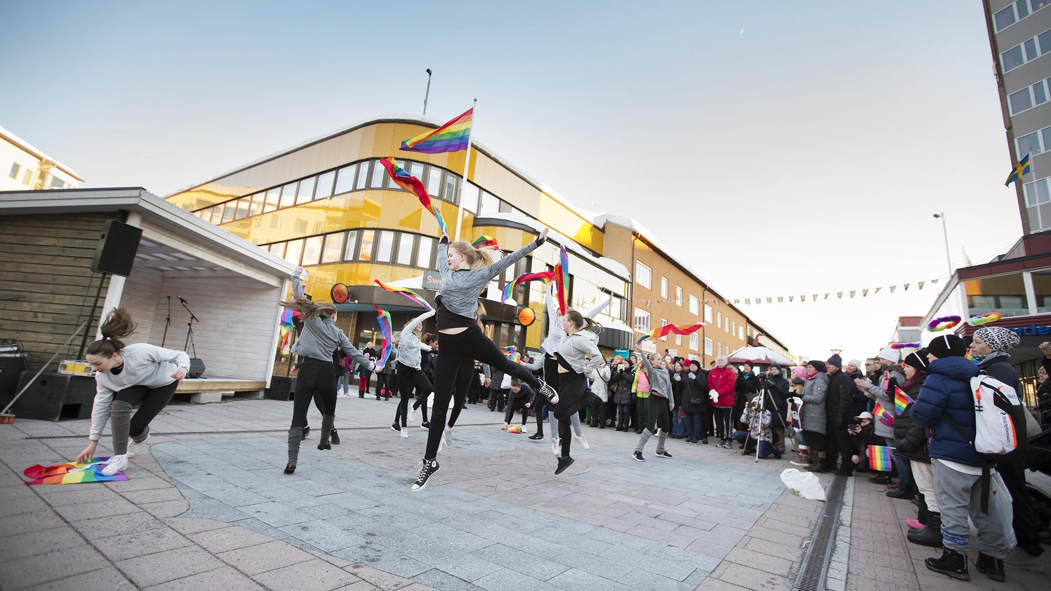 Dansare med prideflaggor dansar på medborgarplatsen i Boden.