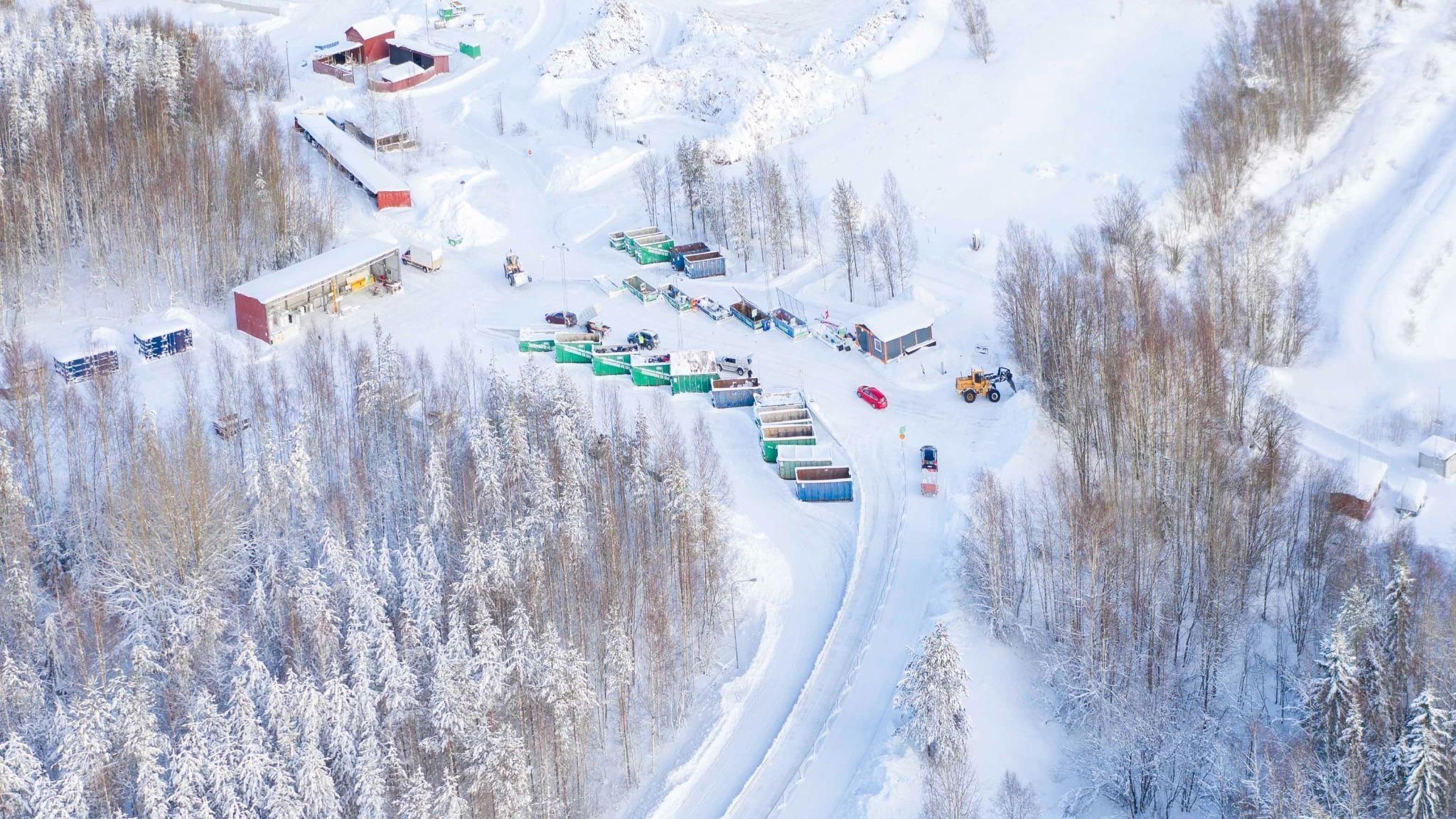 Flygfoto i vintermiljö över återvinningscentral. Ett stort antal containrar står på rad.