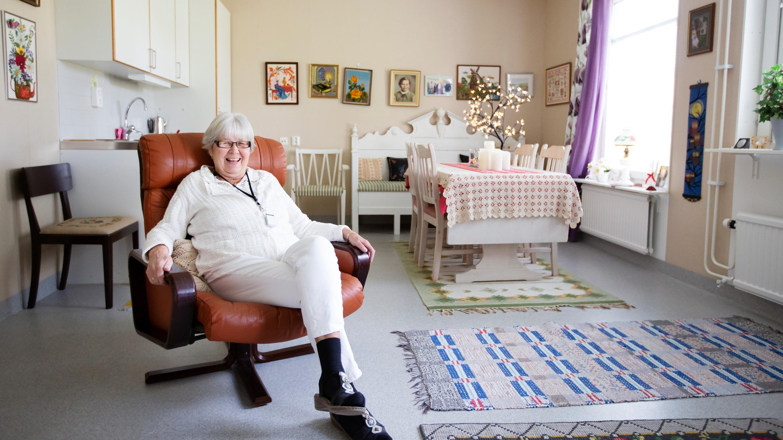 Äldre dam sitter i en fåtölj och skrattar.