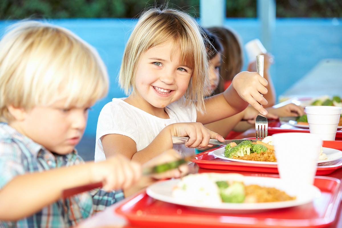 Skolbarn som sitter tillsammans och äter lunch.