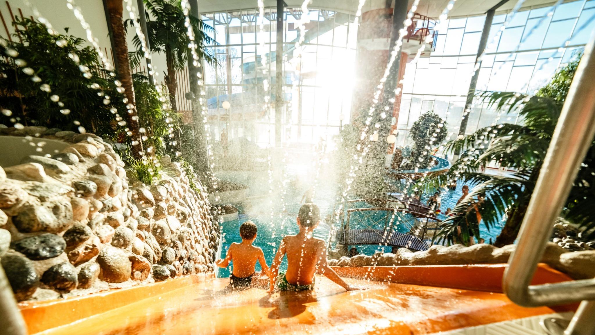 Två barn som åker ned för en vattenrutschkana