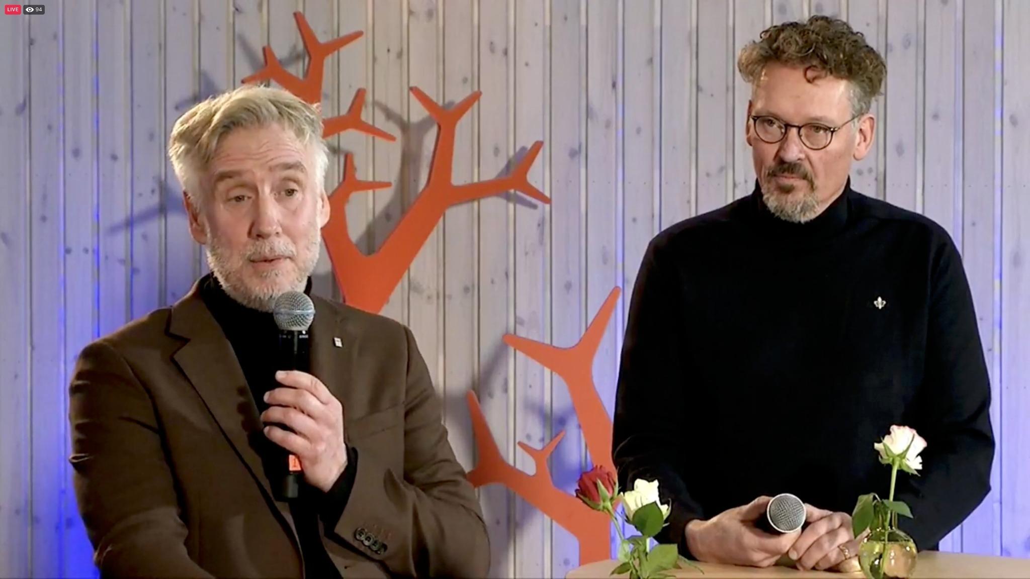 Två män med mikrofoner står på scen. En av dem talar.